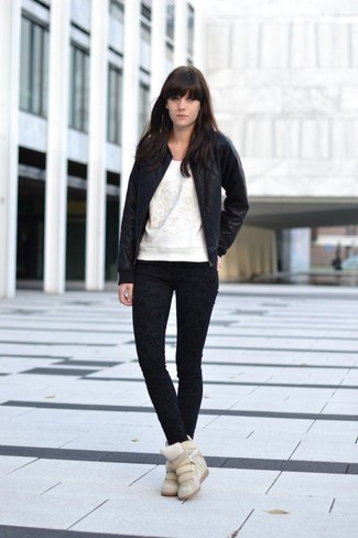 How to wear: black quilted leather bomber jacket, white print sweatshirt, black print skinny jeans, beige suede wedge sneakers