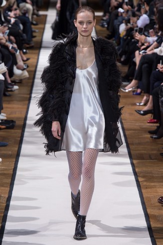 Team a black feather coat with a white satin slip dress for a refined yet off-duty ensemble. Polish off the ensemble with black leather ankle boots.