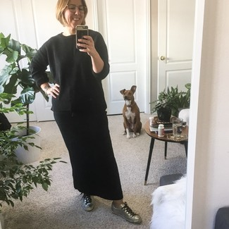 How to Wear a Black Crew-neck Sweater After 40 For Women: If you like off-duty style, why not take this combination of a black crew-neck sweater and a black maxi skirt for a spin? If in doubt as to what to wear in the footwear department, go with a pair of silver leather low top sneakers.