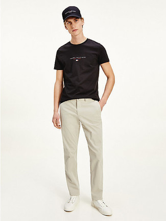 Men's Outfits 2021: Opt for a black print crew-neck t-shirt and beige chinos and you'll be prepared for wherever the day takes you. A pair of white canvas low top sneakers is a smart option to complete this outfit.