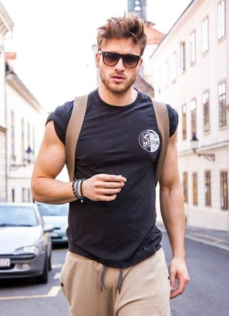 How to wear: black crew-neck t-shirt, beige sweatpants, brown canvas backpack, dark brown sunglasses