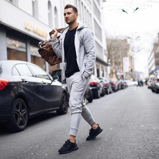 How to wear: black crew-neck t-shirt, grey track suit, black athletic shoes, brown leather holdall