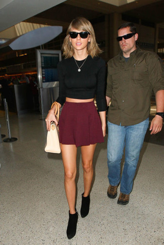 Taylor Swift wearing Black Cropped Sweater, Burgundy Skater Skirt, Black Suede Ankle Boots, Beige Leather Tote Bag
