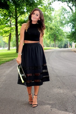 Pairing a black cropped top with a black full skirt is a comfortable option for running errands in the city. Black leather heeled sandals will add elegance to an otherwise simple look.