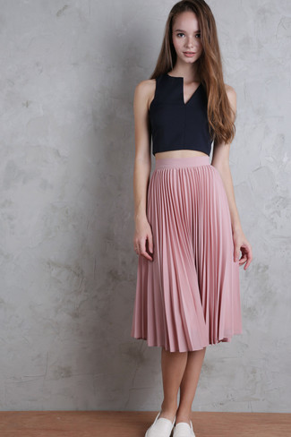 How to Wear White Slip-on Sneakers For Women: If the setting allows off-duty dressing, pair a black cropped top with a pink pleated midi skirt. Send this getup down a sportier path with white slip-on sneakers.