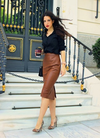 Pairing a black button-up shirt with a skirt is an on-point option for a day in the office. Complement this look with brown python leather pumps.