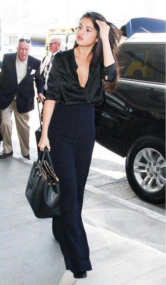 Selena Gomez wearing Black Satin Long Sleeve Blouse, Navy Wide Leg Pants, Black Leather Pumps, Black Leather Tote Bag