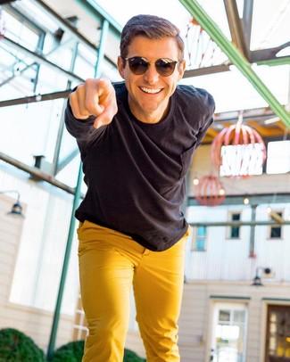 How to wear: black long sleeve shirt, mustard chinos, dark brown sunglasses