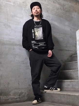 Charcoal Jeans Outfits For Men: A black print long sleeve t-shirt and charcoal jeans are an urban pairing that every style-conscious man should have in his off-duty fashion mix. Complement your ensemble with a pair of black and white leather low top sneakers and you're all done and looking killer.