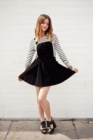 A black overall dress and a white and black horizontal striped long sleeve t-shirt will convey a carefree, cool-girl vibe. Sporting a pair of black leather heeled sandals is a simple way to add extra flair to your outfit. When summer settles in you want to feel comfy and stylish –– this look is just what you need.