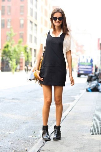 If you're obsessed with comfort dressing when it comes to fashion, you'll love this cute pairing of a River Island Black Denim Overall Dress and a white crew-neck t-shirt. Elevate this look with black leather ankle boots. This is a tested option for an awesome transition look.