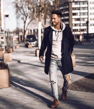 How to wear: black overcoat, grey hoodie, light blue ripped skinny jeans, brown suede casual boots