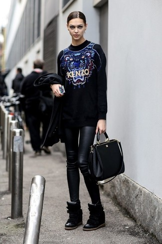 A black print oversized sweater and black leather leggings is a great combination to add to your casual lineup. Dress up this look with black leather wedge sneakers. An outfit like this makes it easy to embrace weird transitional season.