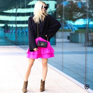 How to Wear a Black Knit Oversized Sweater: A black knit oversized sweater and a hot pink ruffle mini skirt are a cool combo to have in your casual lineup. And if you need to easily lift up your outfit with a pair of shoes, add brown leopard suede ankle boots to the mix.