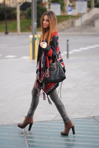 How to wear: black print poncho, grey skinny jeans, brown leather lace-up ankle boots, black leather tote bag