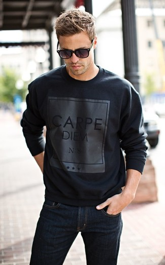 For an everyday outfit that is full of character and personality wear a black graphic round-neck sweater with navy jeans.