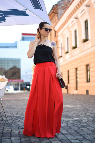 This combination of a black silk sleeveless top and red flare pants is perfect for off-duty occasions.