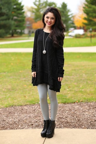 Dress in a black knit sweater dress and grey leggings for an easy to wear look. Elevate your getup with black chunky leather lace-up ankle boots.