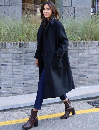 How to Wear Dark Brown Leather Ankle Boots: This combination of a black trenchcoat and navy skinny jeans is super versatile and really up for whatever the day throws at you. Dark brown leather ankle boots are a surefire footwear style here that's full of personality.