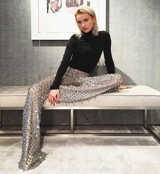 A black turtleneck and gold embellished wide leg pants work together harmoniously. This ensemble is great for summer-to-fall weather.