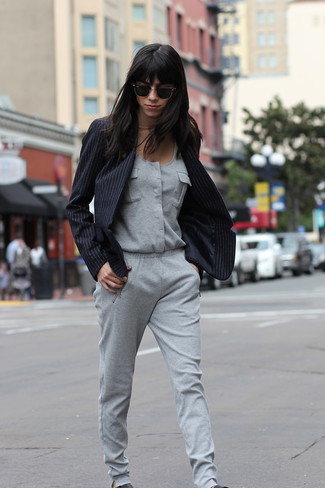 A black striped blazer and a grey jumpsuit are both versatile essentials that will give your outfits a subtle modification. A pair of black leather slip-on sneakers will be a stylish addition to your outfit.