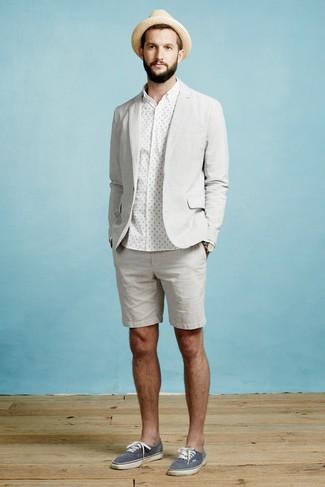 Cómo combinar: blazer gris, camisa de vestir a lunares blanca, pantalones cortos grises, tenis de lona azul marino