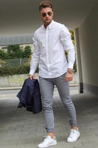 Cómo combinar: blazer azul marino, camisa de vestir blanca, vaqueros pitillo grises, tenis de cuero blancos