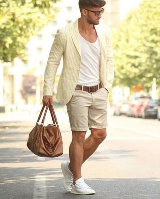 Cómo combinar: blazer de algodón de rayas verticales amarillo, camiseta con cuello circular blanca, pantalones cortos en beige, tenis de lona blancos