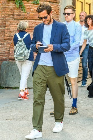 How to Wear Olive Chinos In Summer: This combo of a navy blazer and olive chinos is the perfect base for an infinite number of casually classic ensembles. Get a little creative when it comes to footwear and dial down this look with white leather low top sneakers. This combo is likely to become your summer uniform.