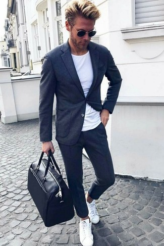 How to Wear a Black Leather Holdall For Men: This bold casual combo of a charcoal knit blazer and a black leather holdall is very easy to throw together without a second thought, helping you look stylish and ready for anything without spending too much time rummaging through your wardrobe. To add elegance to your outfit, finish off with a pair of white low top sneakers.