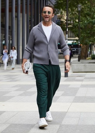 Grey Blazer Outfits For Men: For a casually refined menswear style, team a grey blazer with dark green chinos — these two pieces play really great together. When this look looks too fancy, tone it down by finishing with a pair of white canvas low top sneakers.
