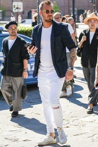 How to Wear White Leather Low Top Sneakers Casually For Men: If you love classic pairings, then you'll love this combo of a navy blazer and white ripped jeans. We love how cohesive this outfit looks when completed with a pair of white leather low top sneakers.