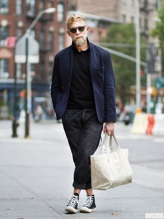 Charcoal Jeans Outfits For Men: When the dress code calls for an elegant yet cool look, you can easily rock a navy blazer and charcoal jeans. Complement this outfit with black and white canvas high top sneakers to keep the getup fresh.