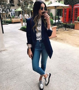 Pair a white and black print crew-neck t-shirt with blue skinny jeans for a refined yet off-duty ensemble. Throw in a pair of silver leather derby shoes for a more relaxed aesthetic. You can bet this look will be your favorite thing when chillier weather hits.