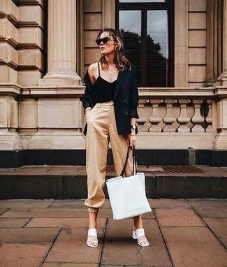 Harmonise un blazer croisé noir avec un pantalon chino brun clair et tu auras l'air d'une vraie poupée. Une paire de des mules en cuir blanches ajoutera de l'élégance à un look simple.