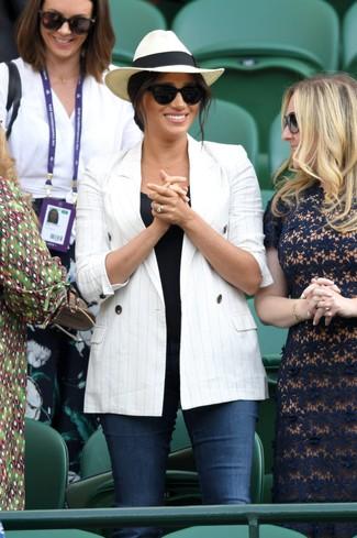 Cómo combinar: blazer cruzado de rayas verticales blanco, camiseta sin manga negra, vaqueros pitillo azul marino, sombrero de paja en beige