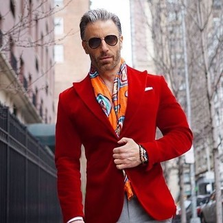 How to wear: red velvet blazer, grey dress pants, orange print scarf, black sunglasses