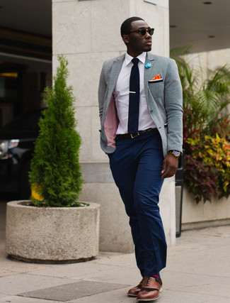 Grey Blazer Outfits For Men: A grey blazer and navy dress pants are among the basic elements of a functional closet. Add a mellow feel to this ensemble by rocking a pair of brown leather brogues.
