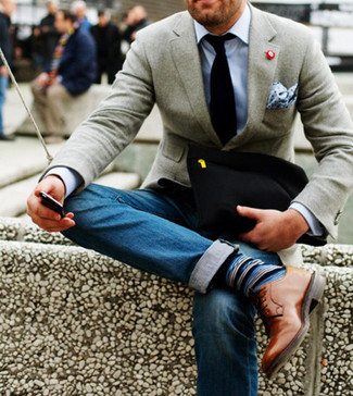 Grey Blazer with Blue Jeans Outfits For Men: This smart combination of a grey blazer and blue jeans is super easy to pull together in no time flat, helping you look awesome and prepared for anything without spending too much time searching through your wardrobe. Balance this getup with a more refined kind of shoes, like these tan leather derby shoes.