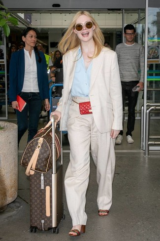 How to Wear a Light Blue Dress Shirt For Women: Loving the way this pairing of a light blue dress shirt and beige linen wide leg pants immediately makes people look seriously chic and classy. As for footwear, complement your getup with multi colored horizontal striped leather heeled sandals.