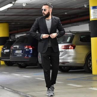 Cómo combinar: blazer negro, jersey con cuello circular gris, pantalón chino negro, tenis de ante grises
