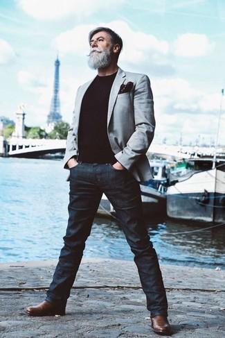 Cómo combinar: blazer gris, jersey con cuello circular negro, vaqueros azul marino, botines chelsea de cuero marrónes