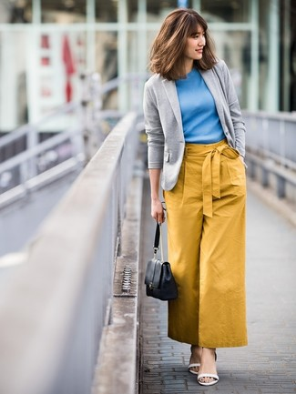 Cómo combinar: blazer de punto gris, jersey de manga corta azul, pantalones anchos mostaza, sandalias de tacón de cuero blancas