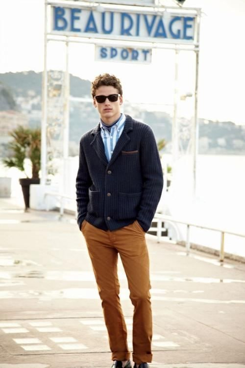 Pairing a navy blue knit blazer with tobacco chinos is an on-point option for
