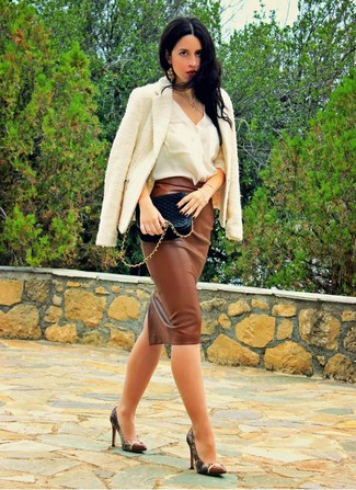 A white tweed blazer and a brown leather midi skirt are both versatile essentials that will give your outfits a subtle modification. Complement this look with brown snake leather pumps.