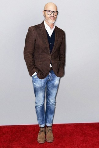 How To Wear Jeans With Boots For Men: This relaxed combination of a dark brown blazer and jeans is a tested option when you need to look stylish in a flash. The whole ensemble comes together when you introduce boots to this look.