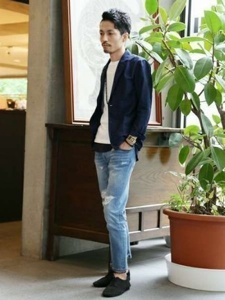 How to Wear Black Canvas Low Top Sneakers For Men: You're looking at the irrefutable proof that a navy blazer and light blue ripped jeans look awesome when worn together in a casual ensemble. Introduce a pair of black canvas low top sneakers to the mix for extra fashion points.