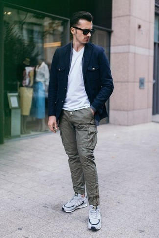 How to Wear a White V-neck T-shirt For Men: We all seek comfort when it comes to styling, and this bold casual combo of a white v-neck t-shirt and olive cargo pants is a good illustration of that. Take your ensemble in a less formal direction with a pair of white and navy athletic shoes.