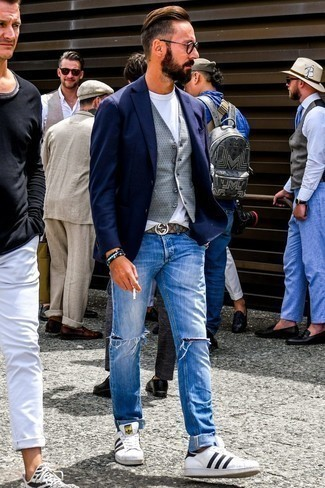 How to Wear White and Black Leather Low Top Sneakers For Men: For an outfit that's pared-down but can be worn in a multitude of different ways, consider wearing a navy blazer and blue ripped jeans. White and black leather low top sneakers integrate well within a variety of getups.