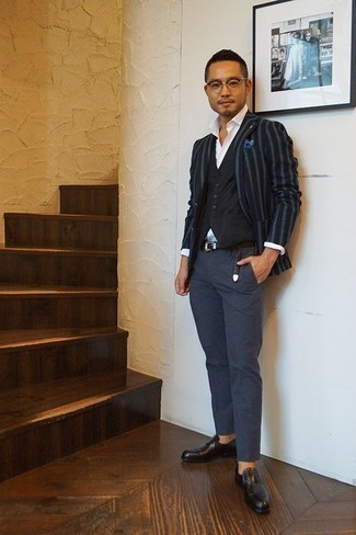 How to Wear a Black Waistcoat: This pairing of a black waistcoat and navy chinos is a life saver when you need to look like an expert in modern men's style. A pair of black leather loafers will be a stylish accompaniment for your ensemble.
